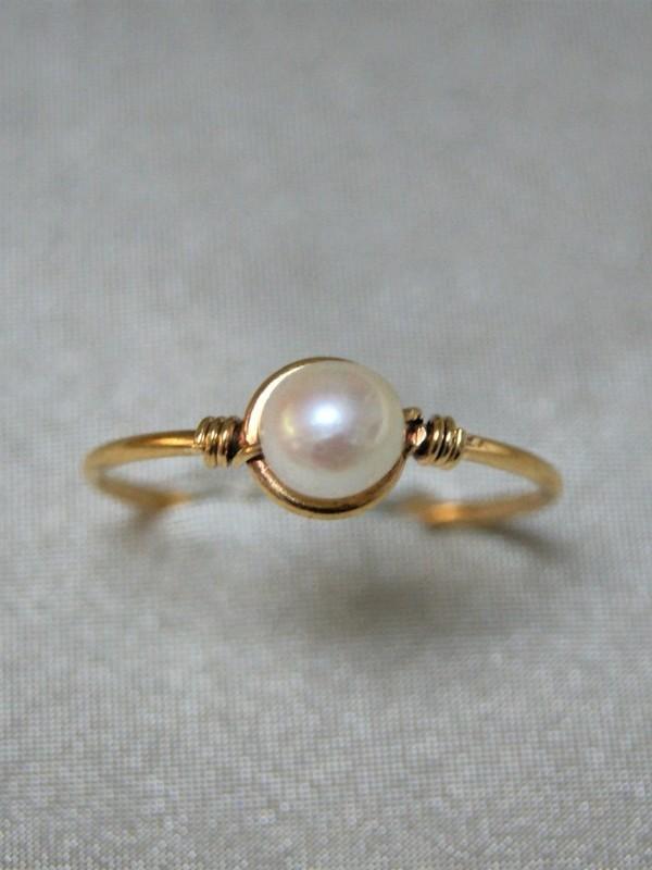 Fijne gouden ring met parel en gedraaide gouden draad aan weerszijden