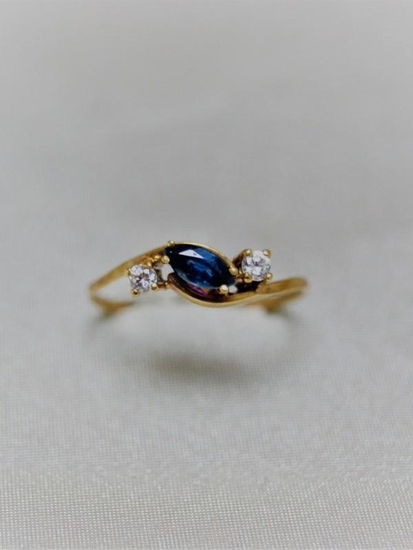 Gouden ring met golvend kopstuk met zirconia en saffier