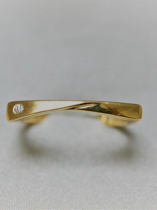Gouden ring met plat en breed kopstuk en met links een briljant