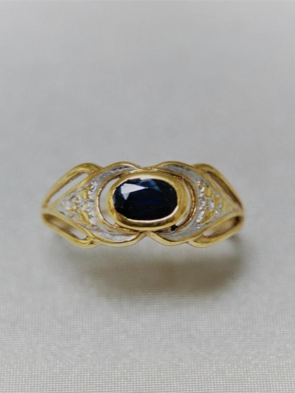 Gouden ring met breed kopstuk en met saffier in kast zetting