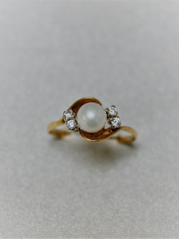 Gouden ring met centaal gezette parel en aan weerszijden zirconia
