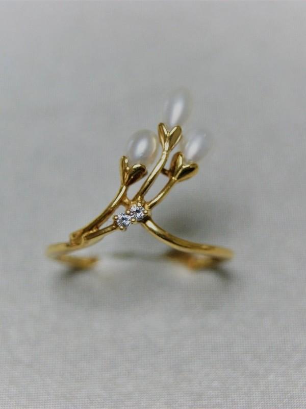 Gouden bloemvormige ring met drie parels en zirconia