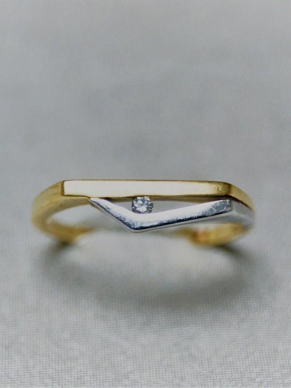 Gouden ring met plat en breed kopstuk en wit gouden rand met span zetting van briljant