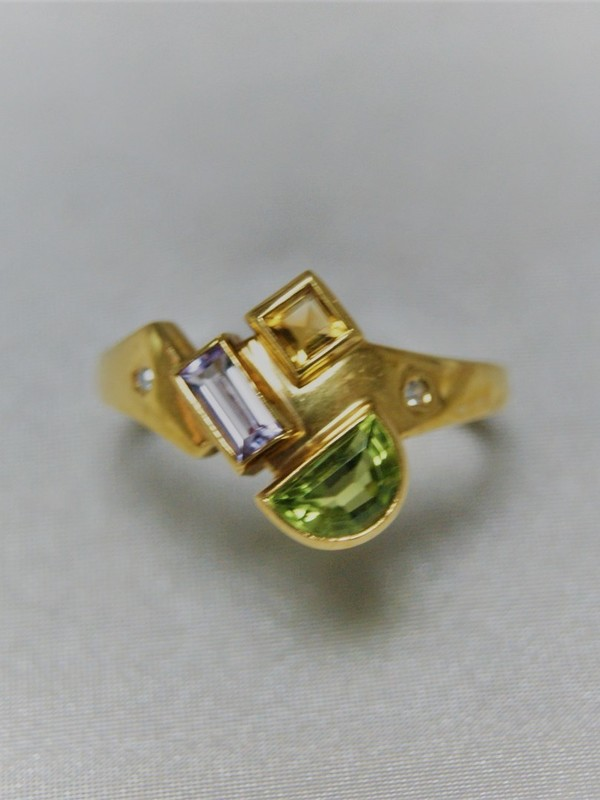 Gouden ring met kast zetting van peridot, citrien en amethist aan weerszijden kleine ingezette zirconium