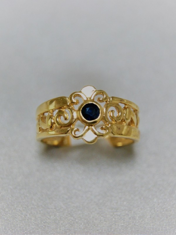Brede gouden ring met saffier in het midden en golvend motief