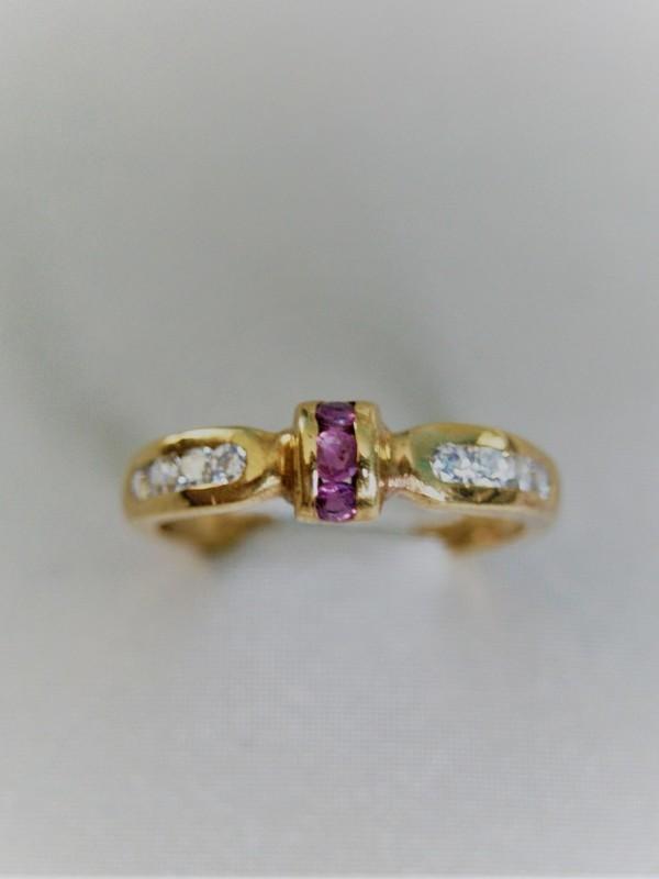Gouden ring met railzetting van zirconia en robijnen